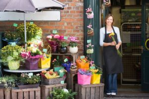A florist standing outside of her shop holding flowers
